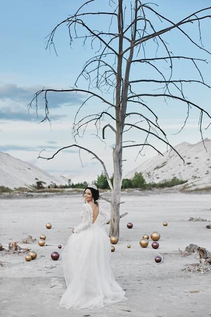 Шикарная молодая модель невесты в модном свадебном платье позирует в соляной пустыне в летний день Premium Фотографии