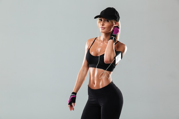 Gorgeous young sports lady standing listening music Free Photo