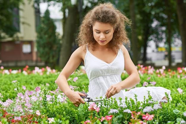 Великолепная молодая женщина, наслаждающаяся садоводством, обрезка растений с ножницами copyspace счастье жизнеспособность позитивность хобби концепция наслаждения природой. Бесплатные Фотографии