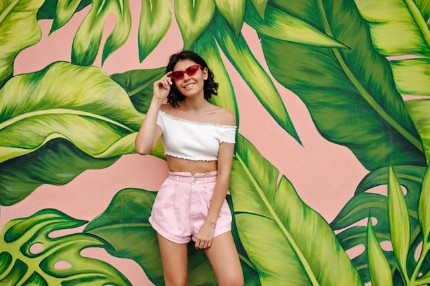 Великолепная молодая женщина в шортах, стоящая перед зелеными граффити Бесплатные Фотографии