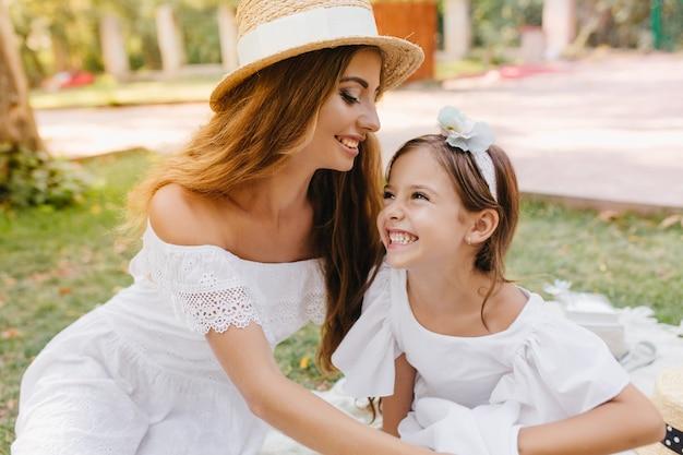額の娘にキスする白いリボンとトレンディな帽子のゴージャスな若い女性。公園で週末を過ごすお母さんと一緒に楽しんでリボンで笑う黒髪の女の子。 無料写真