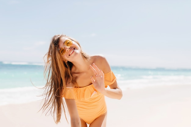 바다 파도와 수평선 감정적으로 포즈 화려한 젊은 여자. 선글라스와 행복을 표현하는 주황색 수영복에 꽤 검은 머리 소녀. 무료 사진