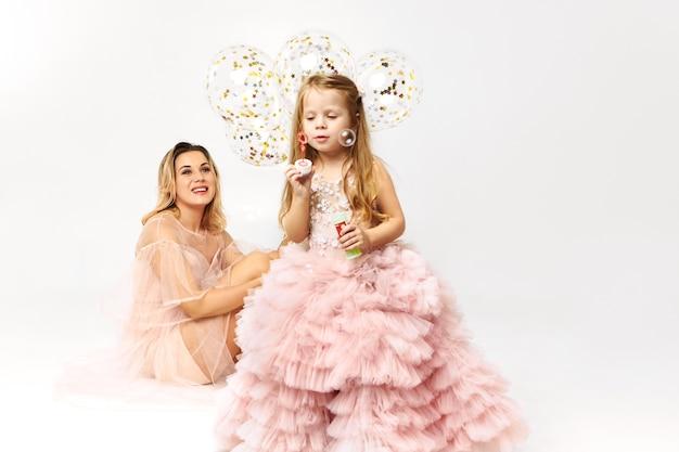 Splendida giovane donna che indossa un abito senza spalline collo basso festeggia il compleanno con sua figlia Foto Gratuite