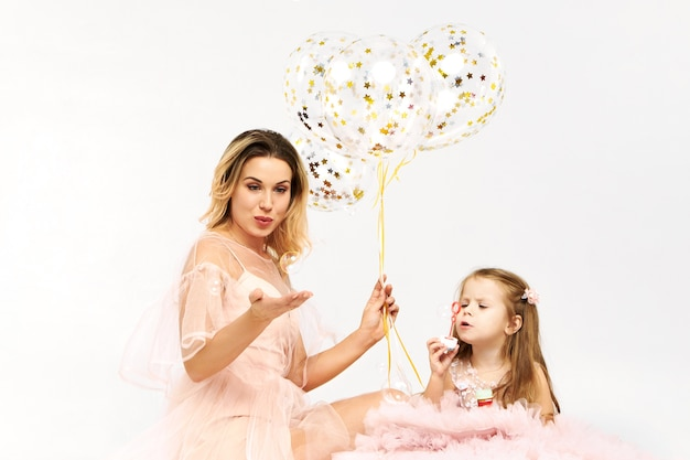 Gorgeous young woman wearing low neck strapless dress celebrating birthday with her daughter Free Photo