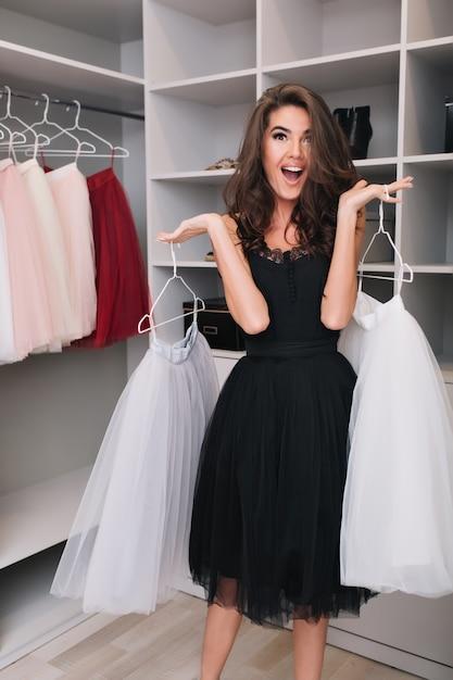 Великолепная молодая женщина со счастливым взглядом, держащая красивые белые пушистые юбки в большом красивом гардеробе, приятно удивлена, шокирована, весела. модная модель в черном платье, элегантный вид. Бесплатные Фотографии
