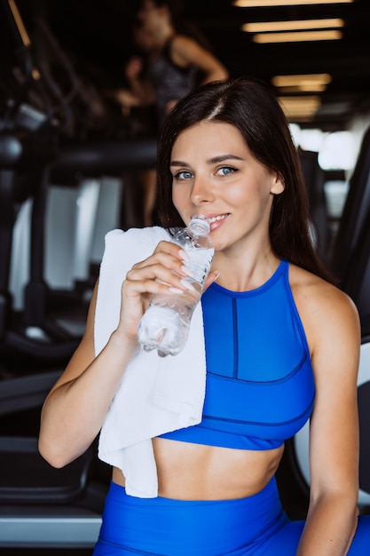 Gorgeous young woman with a towel on her shoulder drinking water from a bottle at the gym Free Photo