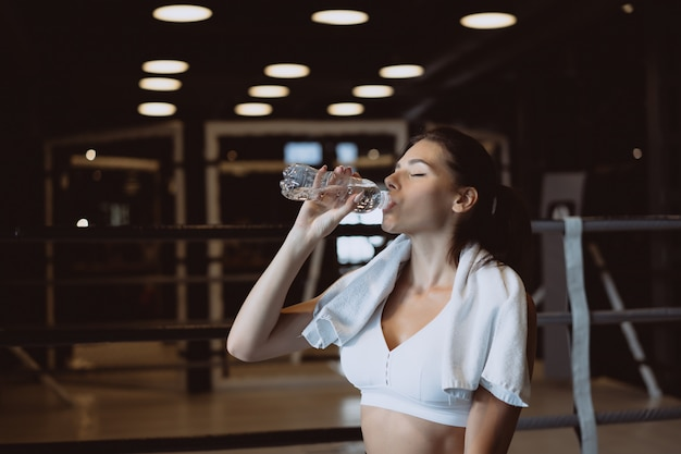Gorgeous young woman with a towel on her shoulders drinking water from a bottle at the gym Free Photo