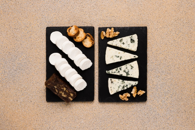 Gorgonzola cheese slices and walnut with goat cheese; brown cheese and bread on black slate stone over textured wallpaper Free Photo