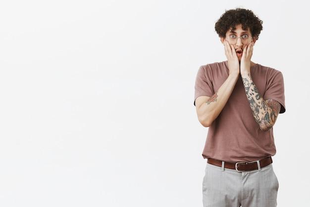 Accidenti che è scioccante. ritratto di stordito di bell'aspetto giovane maschio urbano in scosso con braccio tatuato e baffi in bicchieri tenendo le mani sul viso esprimendo empatia e preoccupazione per il muro grigio Foto Gratuite