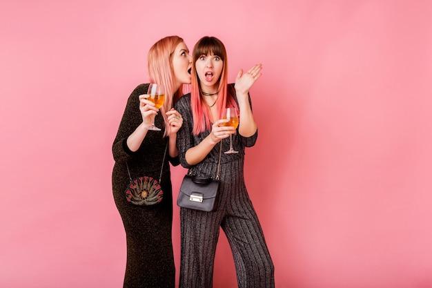 薄ピンクの壁でポーズアルコール飲料のメガネとゴシップガール 無料写真