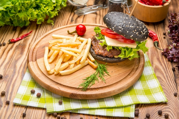 Gourmet black burger with spicy sauce on wooden table Premium Photo