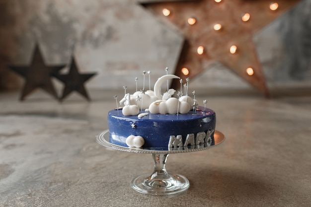 Gourmet blue birthday cake with white decor and candle number one on glass stand in loft Free Photo