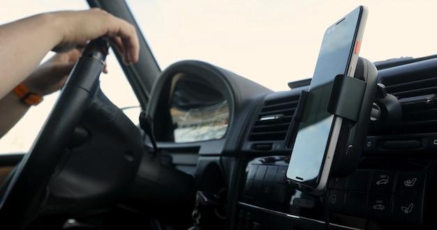 Gps用のダッシュボードに取り付けられたスマートフォンでステアリングホイールに手を繋いでいる車を運転している人 Premium写真