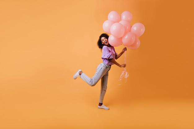 Изящная африканская женская модель в повседневной одежде дурачится на желтом. эмоциональная день рождения девушка танцует с воздушными шарами. Бесплатные Фотографии