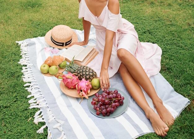 Изящная азиатская женщина, наслаждающаяся летним пикником на зеленой лужайке около бассейна. Бесплатные Фотографии