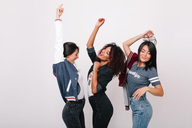 Изящная черная модель танцует между латинскими и азиатскими друзьями и поет любимую песню. фотография в помещении иностранных студентов, весело проводящих время после покупок вместе. Бесплатные Фотографии