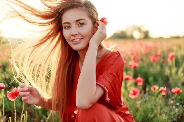 優雅なブロンドの女性は彼女の肩に身を包み、見ています。風の強い髪。暖かい夕日の色の美しいケシ畑。 無料写真