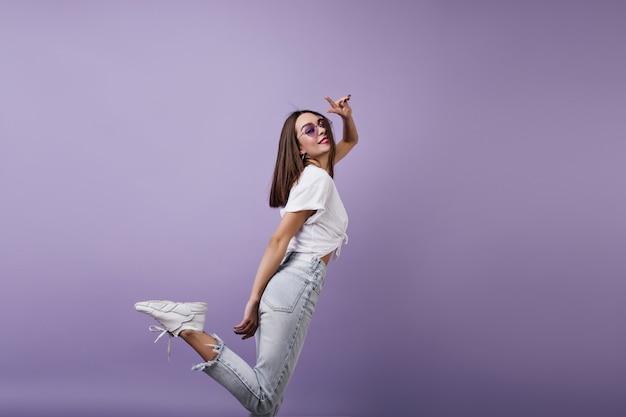 Изящная европейская женщина в модных кроссовках веселится. портрет довольно белой девушки в изолированных джинсах. Бесплатные Фотографии
