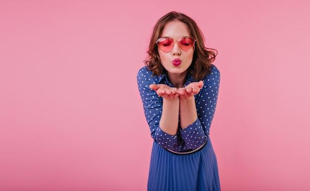 目を閉じてポーズをとってエアキスを送る青いドレスを着た優雅な女の子。キスの表情でピンクの壁に分離された短いウェーブのかかった髪の若い女性。 無料写真