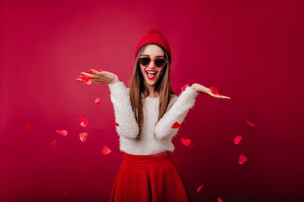 하트 색종이를 던지고 푹신한 스웨터에 우아한 소녀 무료 사진