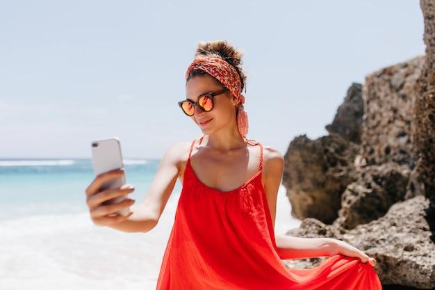 Ragazza graziosa in occhiali da sole scintillanti che fanno selfie nel fine settimana in località estiva. colpo esterno di beata signora abbronzata che si prende una foto di se stessa mentre si rilassa a ocean beach. Foto Gratuite