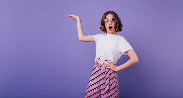 写真撮影中に驚きの感情を表現するウェーブのかかった茶色の髪の優雅な女の子。手を上げて紫色の壁に立っている眼鏡をかけた白人の驚いた女性の屋内肖像画。 無料写真