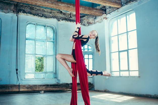 Graceful gymnast performing aerial exercise with red fabrics on blue old loft background. Free Photo