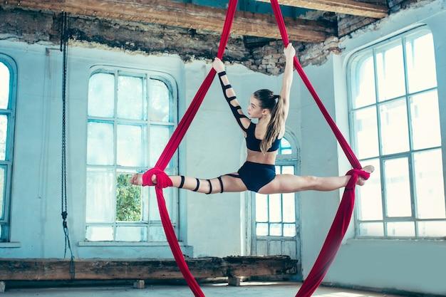 Изящная гимнастка, выполняющая воздушные упражнения с красными тканями на синем старом фоне чердака. молодая предназначенная для подростков кавказская подходящая девушка. цирк, акробатика, акробат, артист, спорт, фитнес, гимнастическая концепция Бесплатные Фотографии