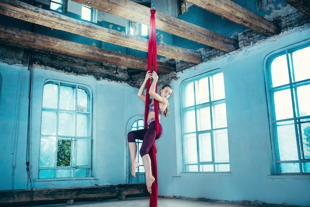 青い古いロフトの背景に赤い布で空中運動を実行する優雅な体操選手。 無料写真