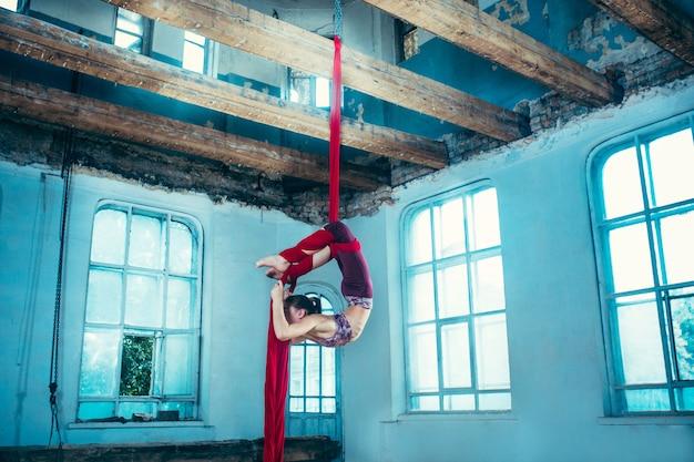Изящная гимнастка выполняет воздушные упражнения с красными тканями на синем старом чердаке Бесплатные Фотографии