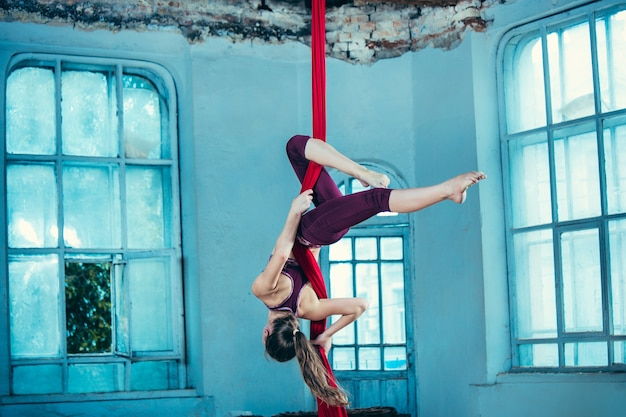 Graceful gymnast performing aerial exercise with red fabrics Free Photo