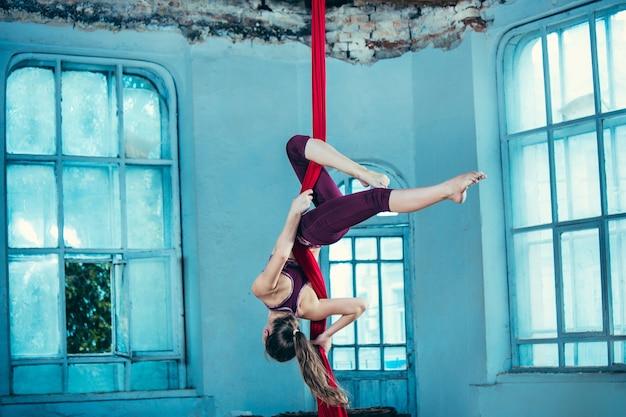 赤い布で空中運動を行う優雅な体操選手 無料写真