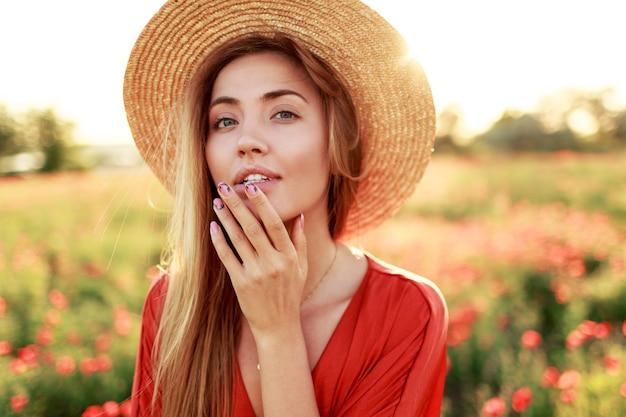 Изящная длинноволосая женщина смотрит на горизонт, наслаждаясь свободой. соблазнительная девушка позирует в маковом поле. теплый закатный свет. Бесплатные Фотографии