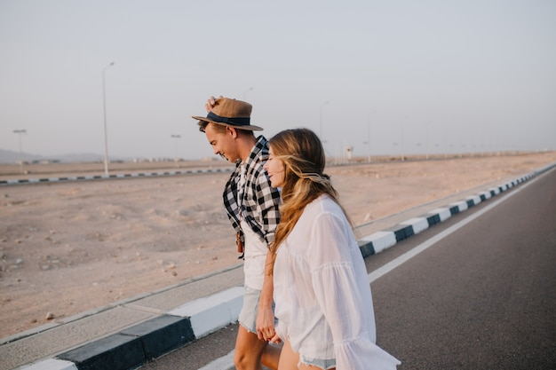Graceful long-haired woman in white shirt and boy in hat walking down the highway holding hands and smiling. stylish couple crosses the road and talking about travel under open sky in early morning Free Photo