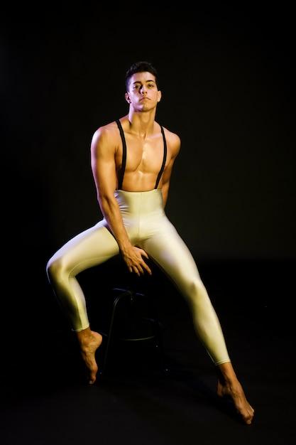 Graceful male ballet dancer resting in spotlight Free Photo
