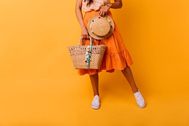 스튜디오에서 포즈 여름 가방 우아한 무두 질된 소녀. 트렌디 한 모자를 들고 긴 치마에 평온한 여성 모델. 무료 사진