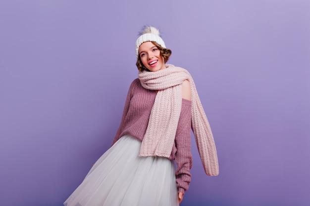 Graziosa ragazza bianca in sciarpa lunga e calda in piedi sulla parete viola. raffinata giovane donna soddisfatta in cappello in posa con il sorriso. Foto Gratuite