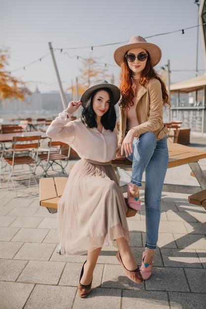 親友とストリートカフェに座っているロングスカートの優雅な女性 無料写真