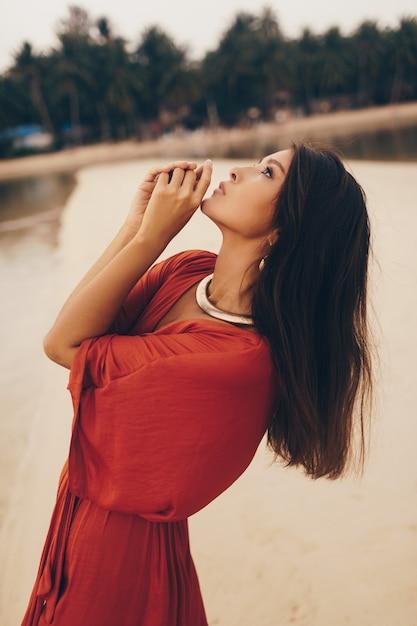 Грациозная женщина позирует на пляже, сидя на песке в красном платье Бесплатные Фотографии