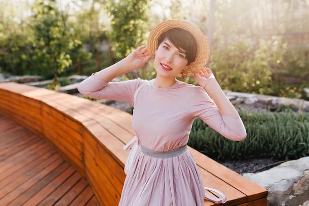 Graziosa giovane signora in abiti vintage volentieri in posa nel parco godendo la luce del sole Foto Gratuite