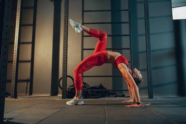 Изящный. молодая мускулистая кавказская женщина упражнениями в тренажерном зале. спортивная (ый) женская модель делает силовые упражнения, тренирует нижнюю, верхнюю часть тела, растяжку. велнес, здоровый образ жизни, бодибилдинг. Бесплатные Фотографии