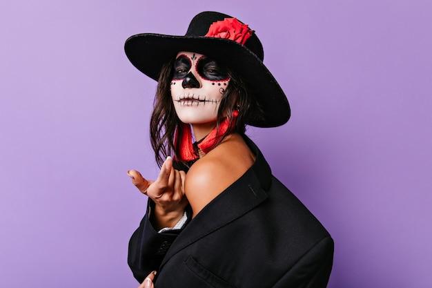 Изящная молодая женщина в черном сомбреро стоя на фиолетовой стене. беззаботная брюнетка девушка с нежно улыбается хэллоуин макияж. Бесплатные Фотографии