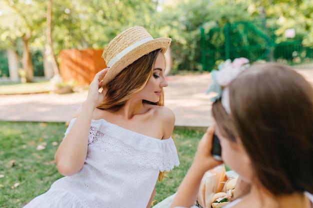 娘の前で目を閉じてポーズをとるエレガントなヴィンテージドレスの優雅な若い女性。カメラを保持し、母親の写真を作る黒髪の少女 無料写真