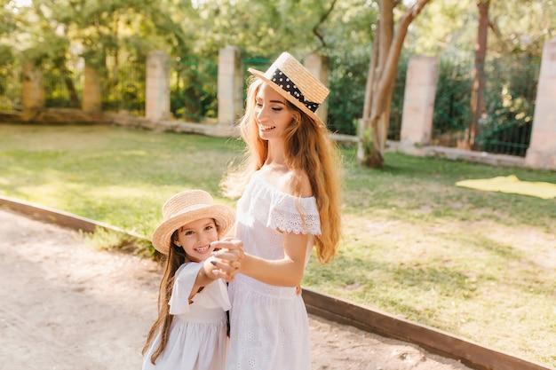 Graziosa giovane donna in abito bianco ballando con la figlia sul vicolo e sorridente. ritratto all'aperto di mamma affascinante in barca di paglia tenendosi per mano con bambino gioioso voleva giocare. Foto Gratuite