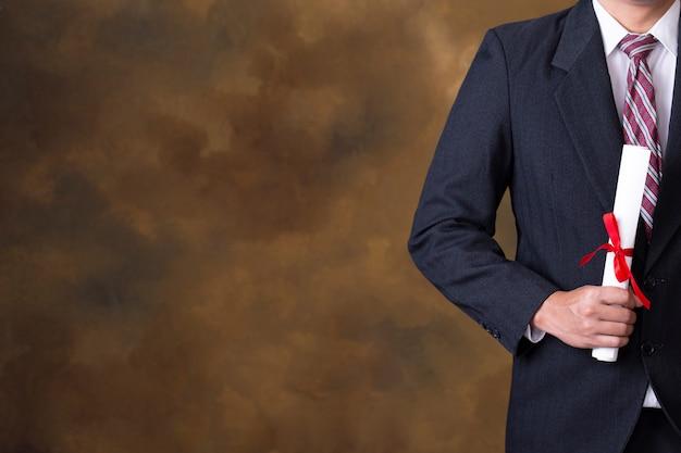 Graduate man holding degree. copyspace. Premium Photo