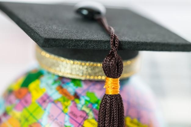 Graduate study abroad concept, graduation cap on top earth globe model map Premium Photo