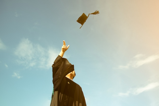 A graduate threw a hat up to sky of graduation ceremony in graduation day Premium Photo