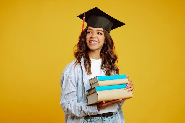 黄色の本で彼女の頭に卒業の帽子の大学院の女性。 Premium写真