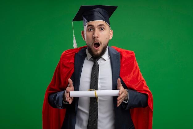 Uomo laureato in mantello rosso con diploma di essere stupito e sorpreso in piedi oltre la parete verde Foto Gratuite