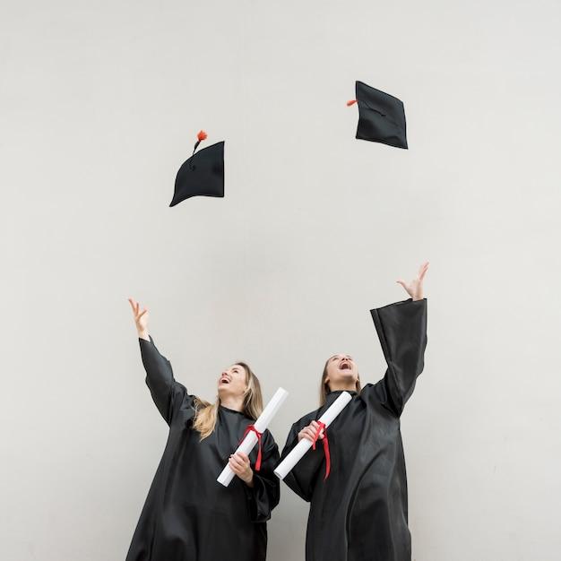 Graduates throwing their trenchers Free Photo
